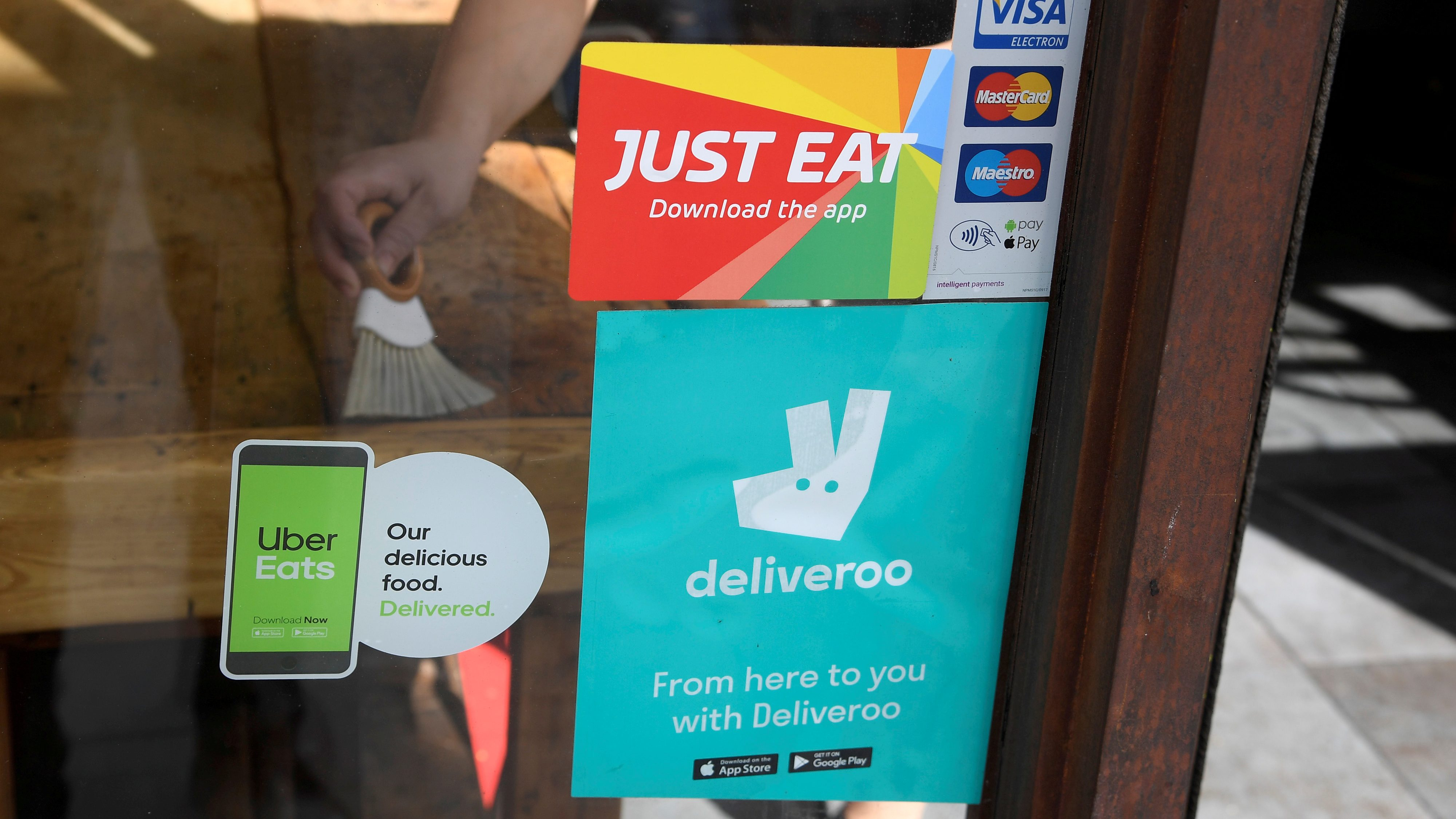 Signage for Just Eat is seen next to Uber Eats and Deliveroo advertisements on the window of a restaurant in London,