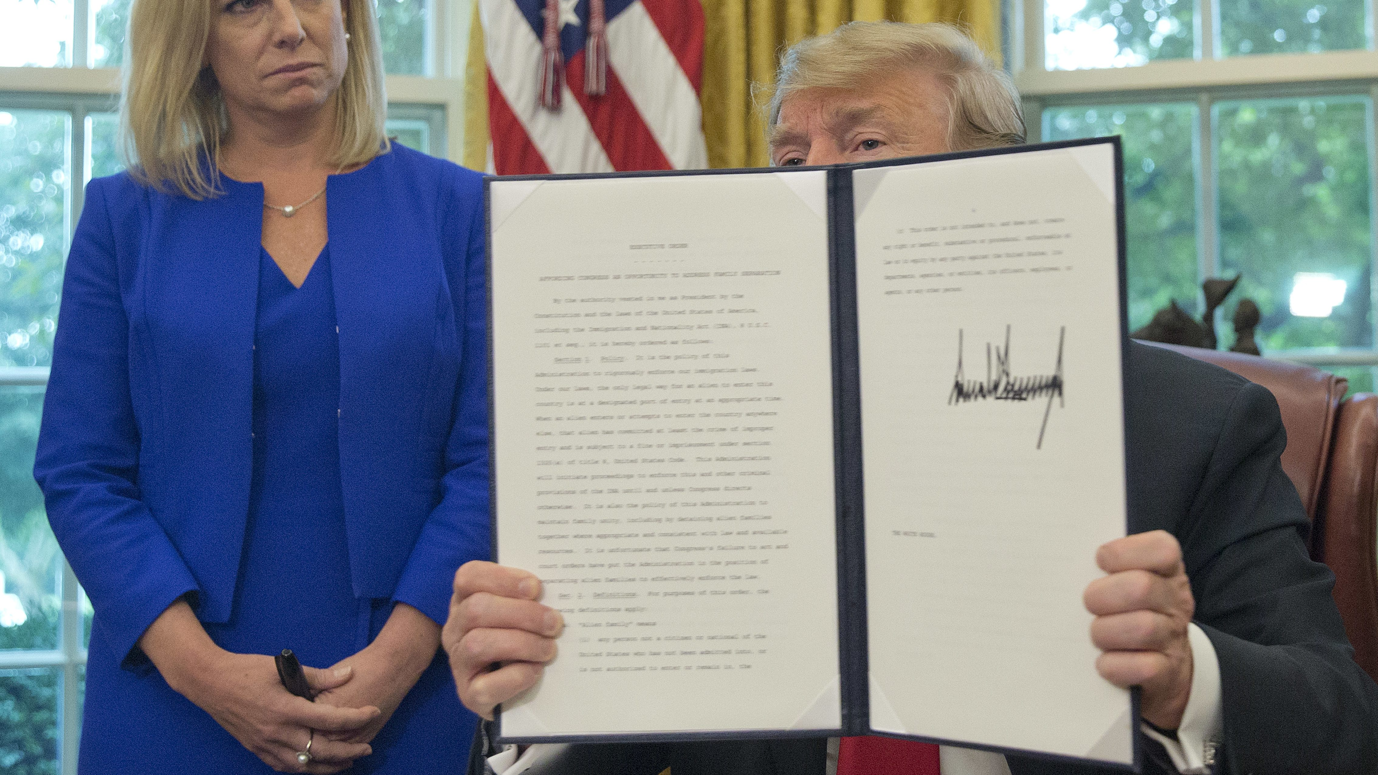 President Donald Trump holds up an executive order he signed to end family separations, during an event in the Oval Office of the White House in Washington, Wednesday, June 20, 2018. Looking on is Homeland Security Secretary Kirstjen Nielsen, left.
