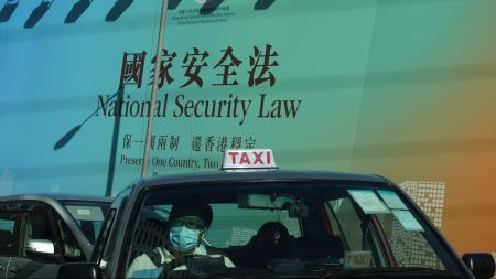 A taxi drives past a big banner featuring the Hong Kong National Security Law in Hong Kong, Monday, June 29, 2020.