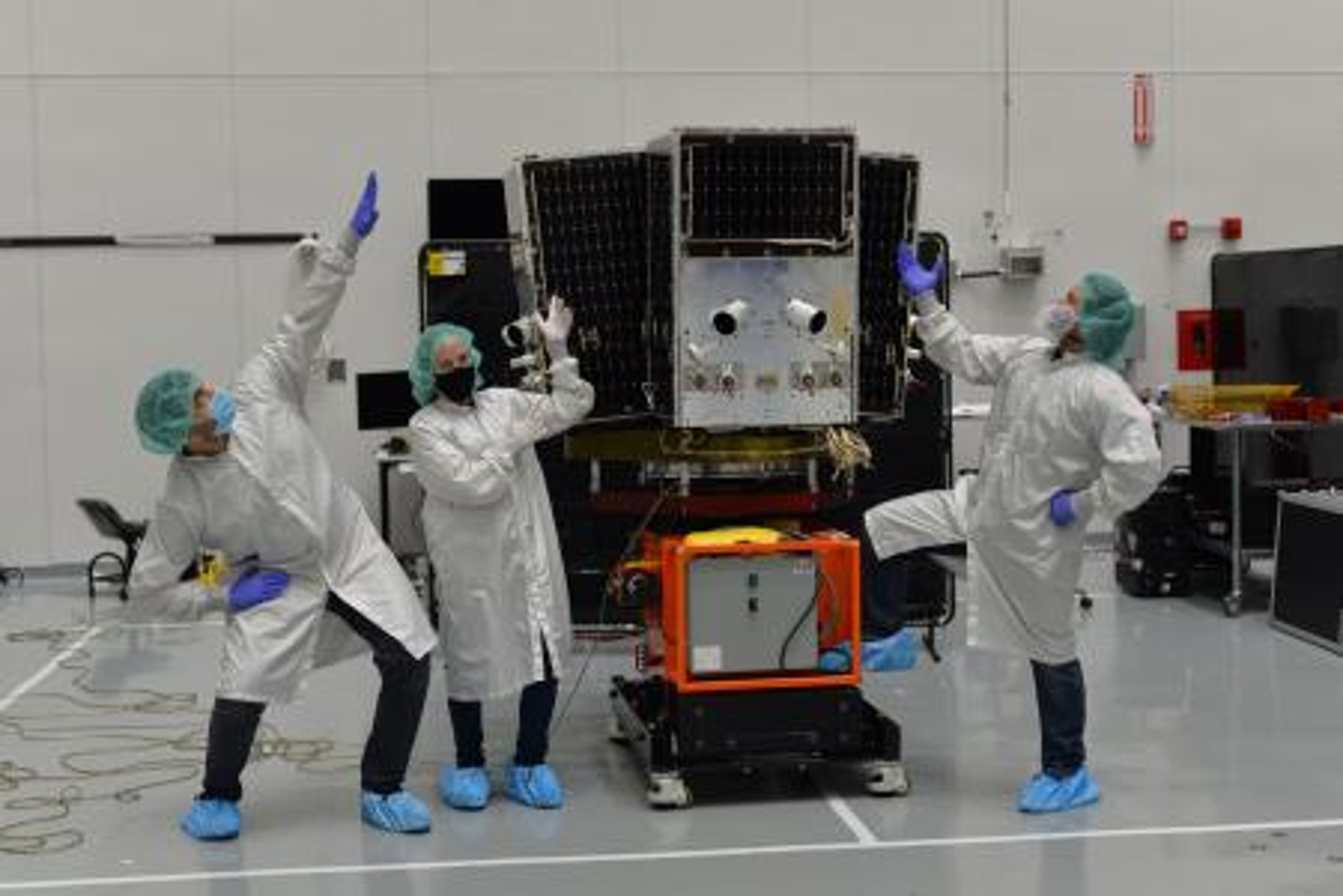 Planet staff Michael Soulage, Natasha Nogueira, Raul Antonio Perez prepare a SkySat for launch.