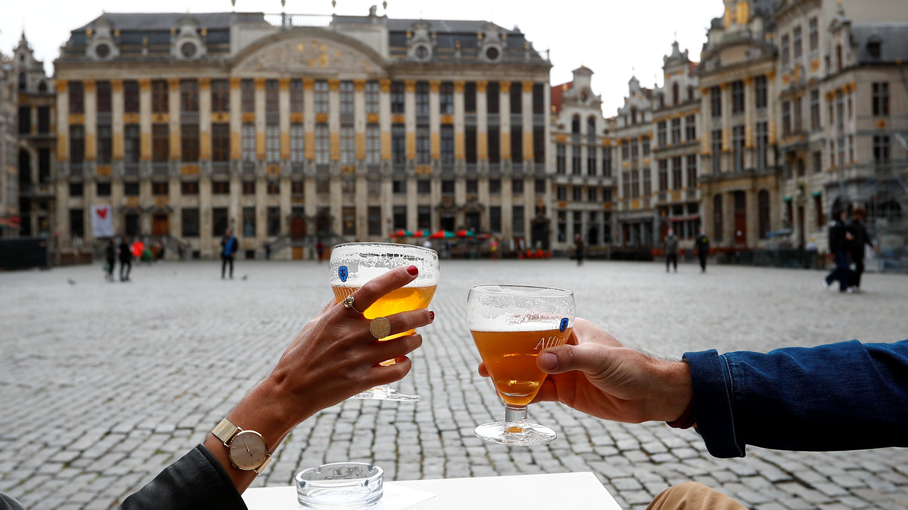 Two people having a beer in a square in Brussels