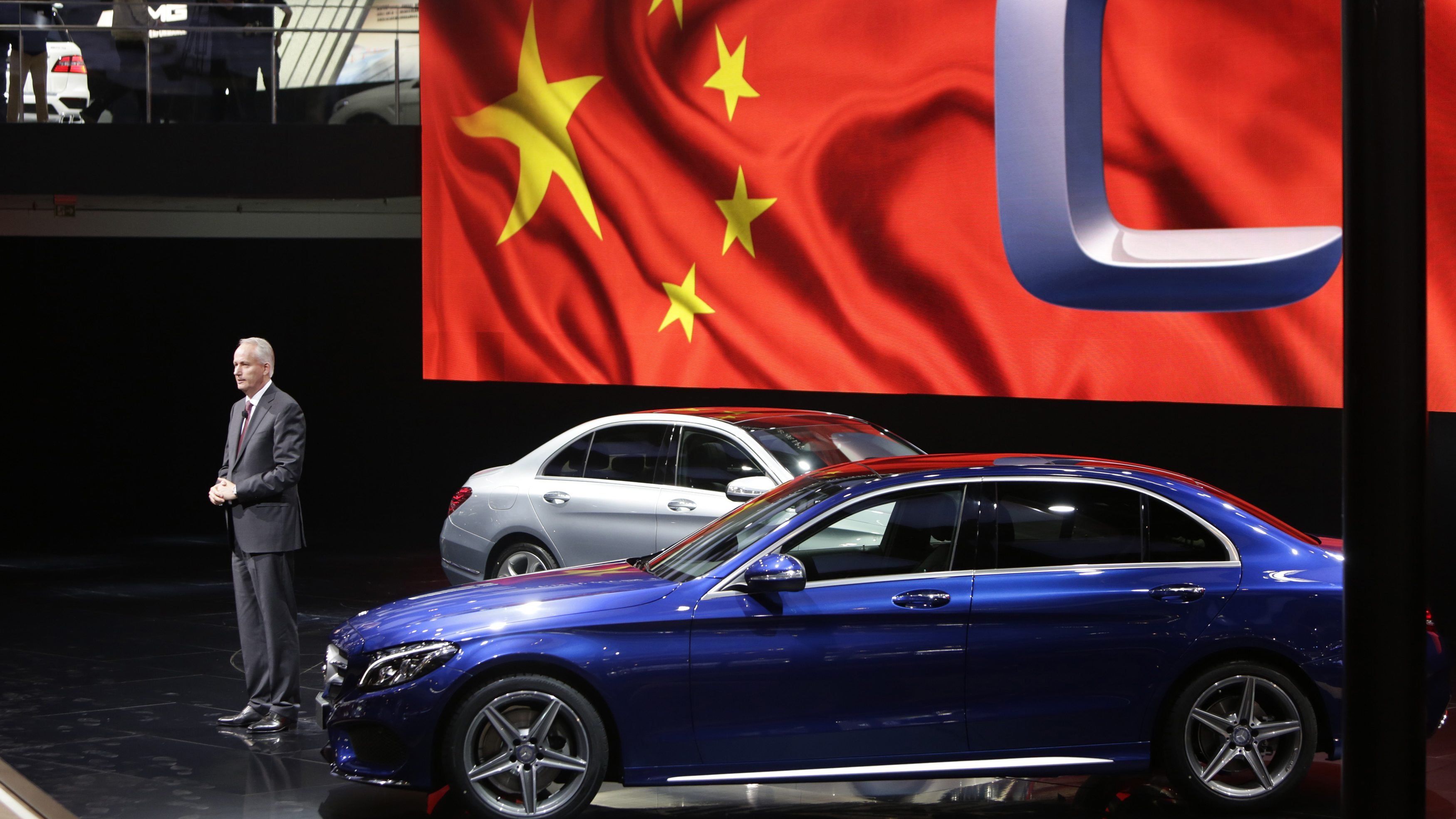 A Daimler board member presents a new car in front of a projection of a Chinese flag.