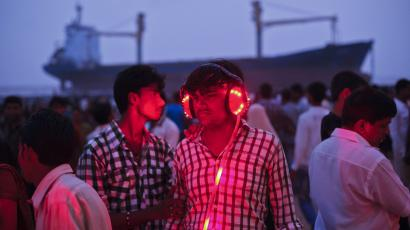 Man wears a headset while listening to a fortune telling machine as people flock to Juhu Beach at low tide to see a cargo ship which ran aground due to rough weather in Mumbai