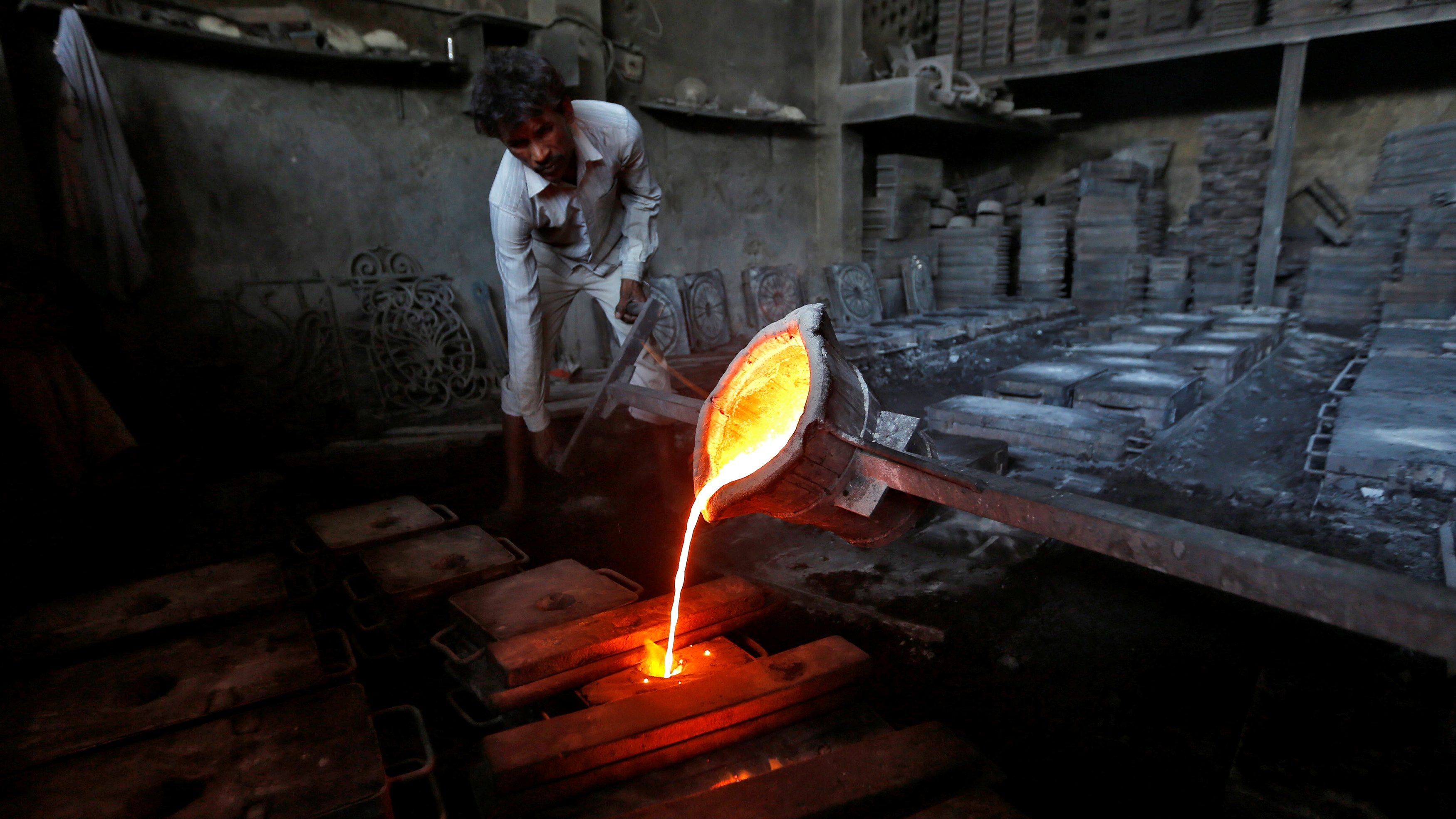 A worker pours molten iron from a ladle to make lamp posts inside an iron casting factory in Ahmedabad
