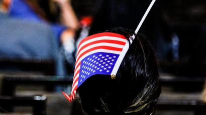 A woman puts an American flag in her hair as the guests of the Israeli-American Council Summit await the arrival of U.S. President Donald Trump in Hollywood