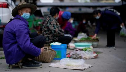 Street vendors wearing face masks wait for customers at their vegetable stalls in Jingzhou, after the lockdown was eased in Hubei province, the epicentre of China's coronavirus disease (COVID-19) outbreak, March 27, 2020.