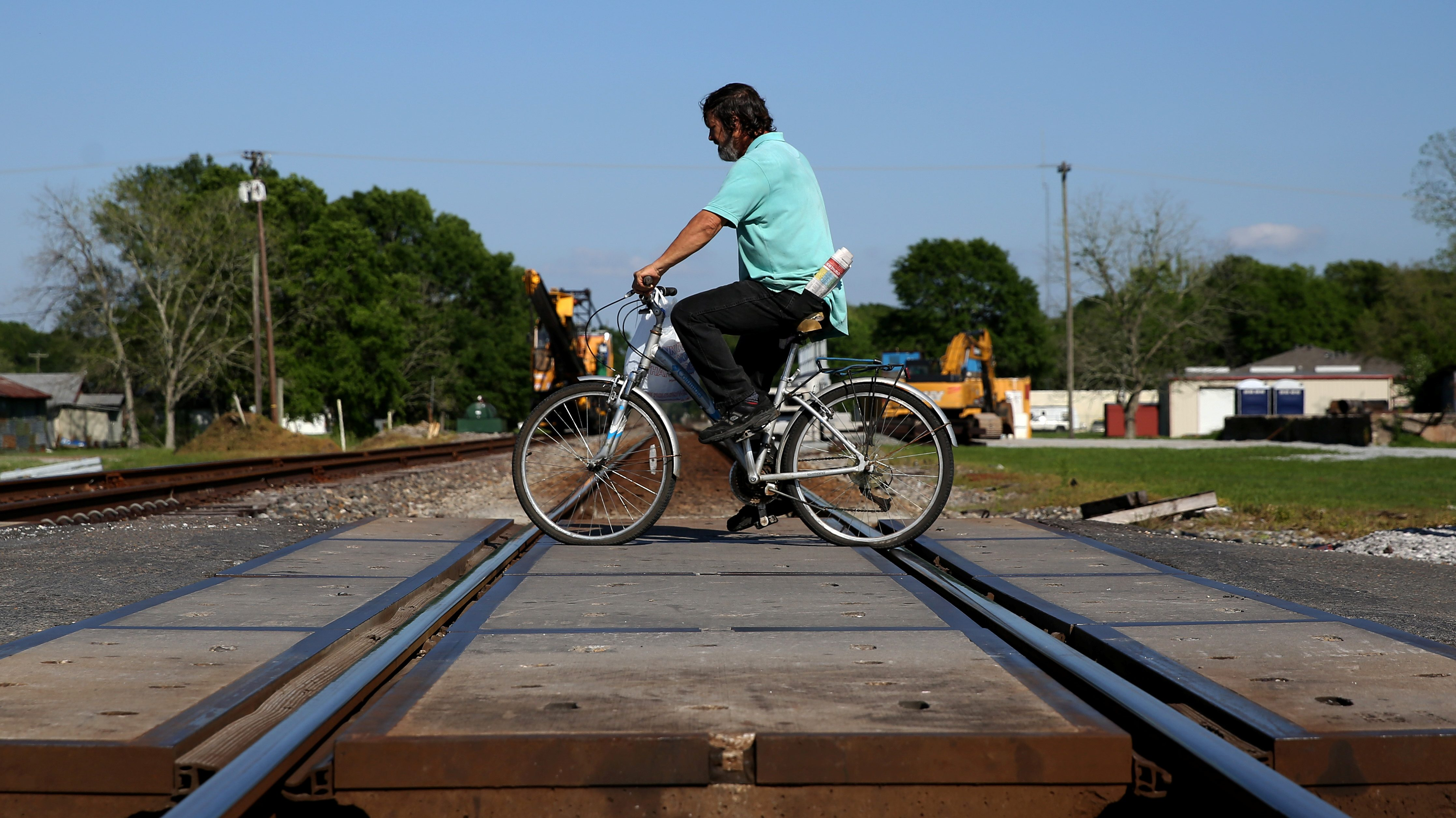 A man rides his bike over rail road tracks in rural Louisiana