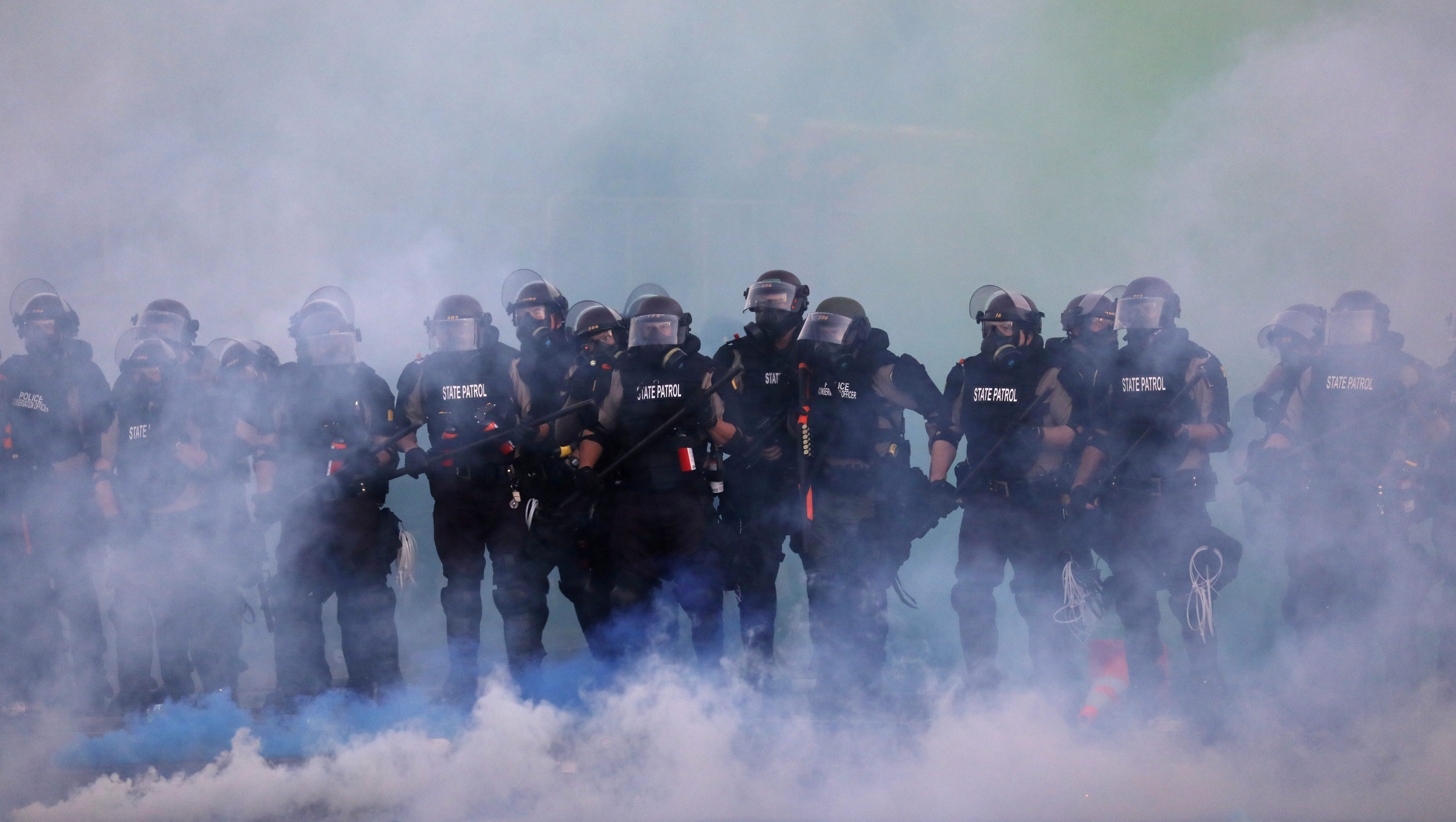 olice officers are seen amid tear gas as protesters continue to rally against the death in Minneapolis police custody of George Floyd