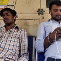 Two Indian men watch videos on their mobile phones as they travel in a suburban train in Mumbai