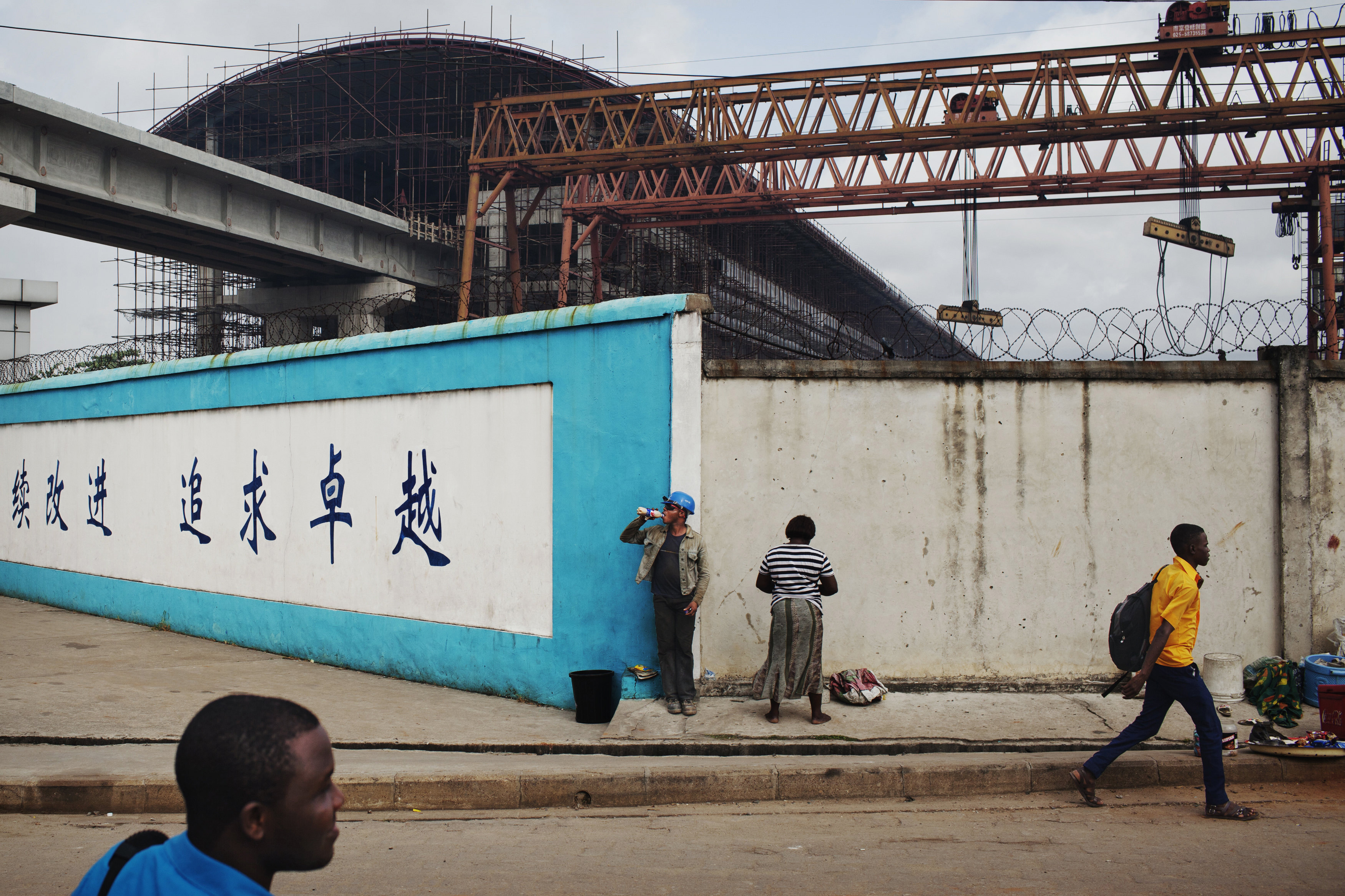 Pedestrians pass by a construction site of Lagos Rail Mass Transit system in Lagos in 2013.