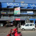 A scooterist rides past a shopping complex with the billboard of Chinese smartphone maker Vivo in Ahmedabad