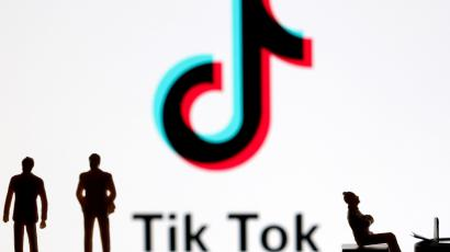 A 3-D printed figures are seen in front of displayed Tik Tok logo in this picture illustration