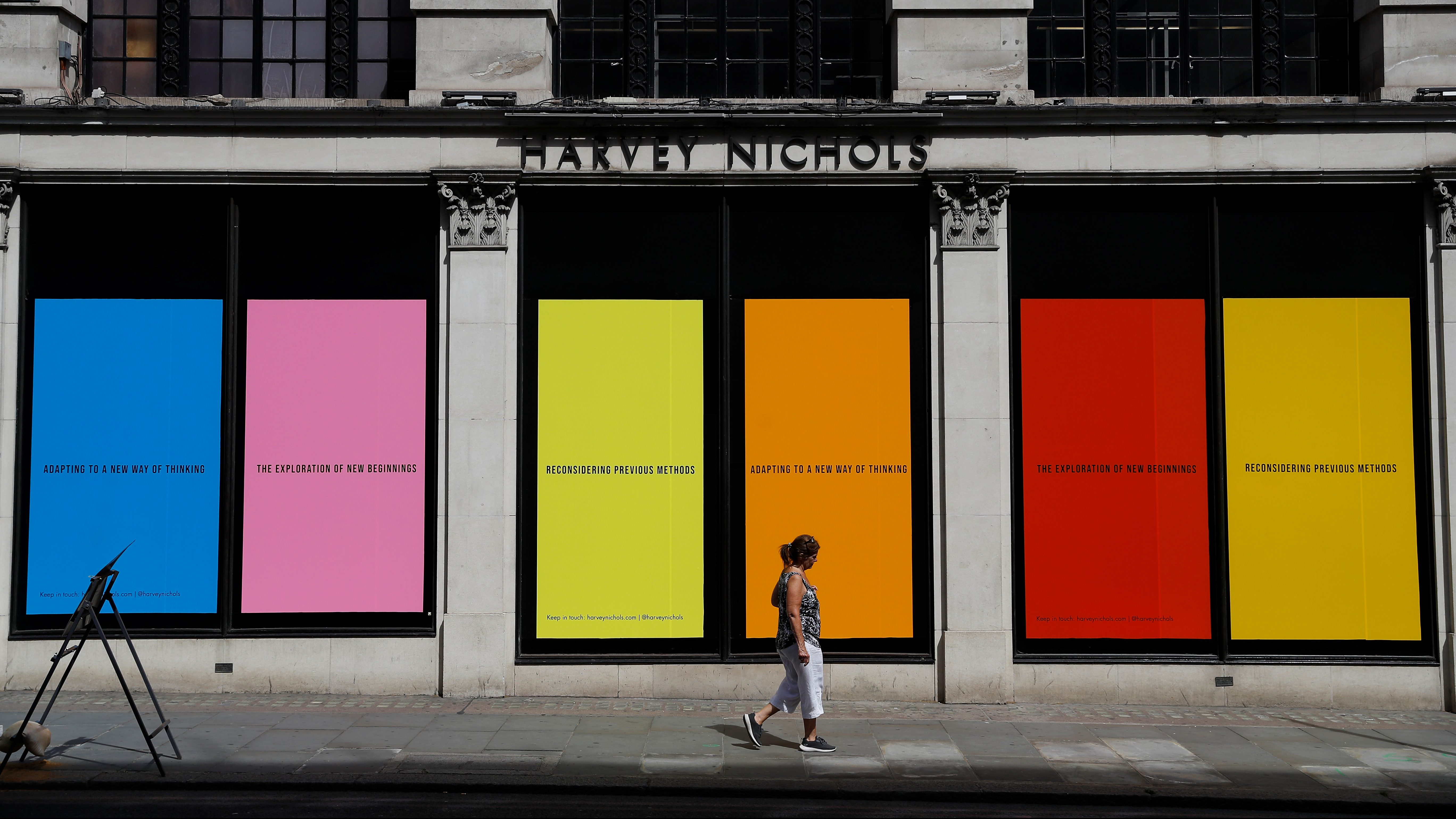 A woman walks by a closed Harvey Nichols store in London