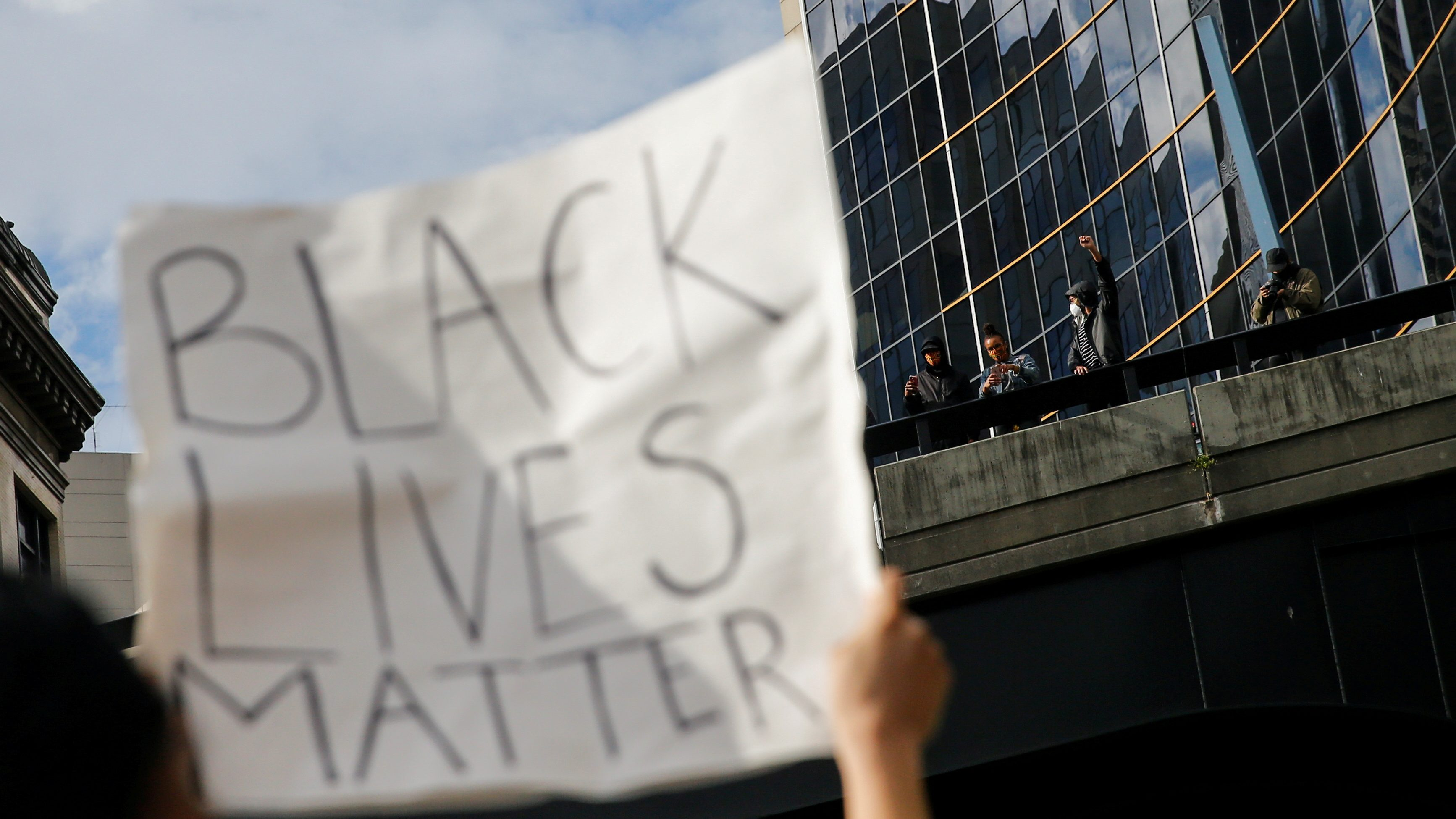 A protester holds a Black Lives Matter sign in front of an office building