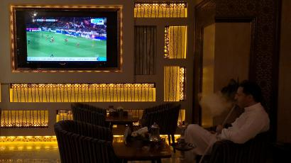 A Saudi man smokes shisha while watching a broadcast of Bundesliga highlights, pirated by beoutQ, at a local cafe in Khobar