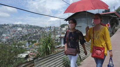 Naga girls wearing face masks walk on a street in Kohima,