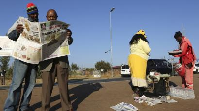 Men read a newspaper next to a stall in Soweto