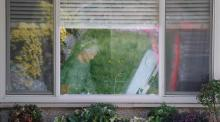 An elderly woman with a mask on looking out of her nursing home window.