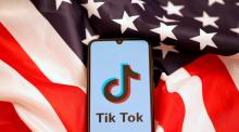 Tik Tok logo is displayed on the smartphone while standing on the U.S. flag in this illustration picture taken, November 8, 2019.