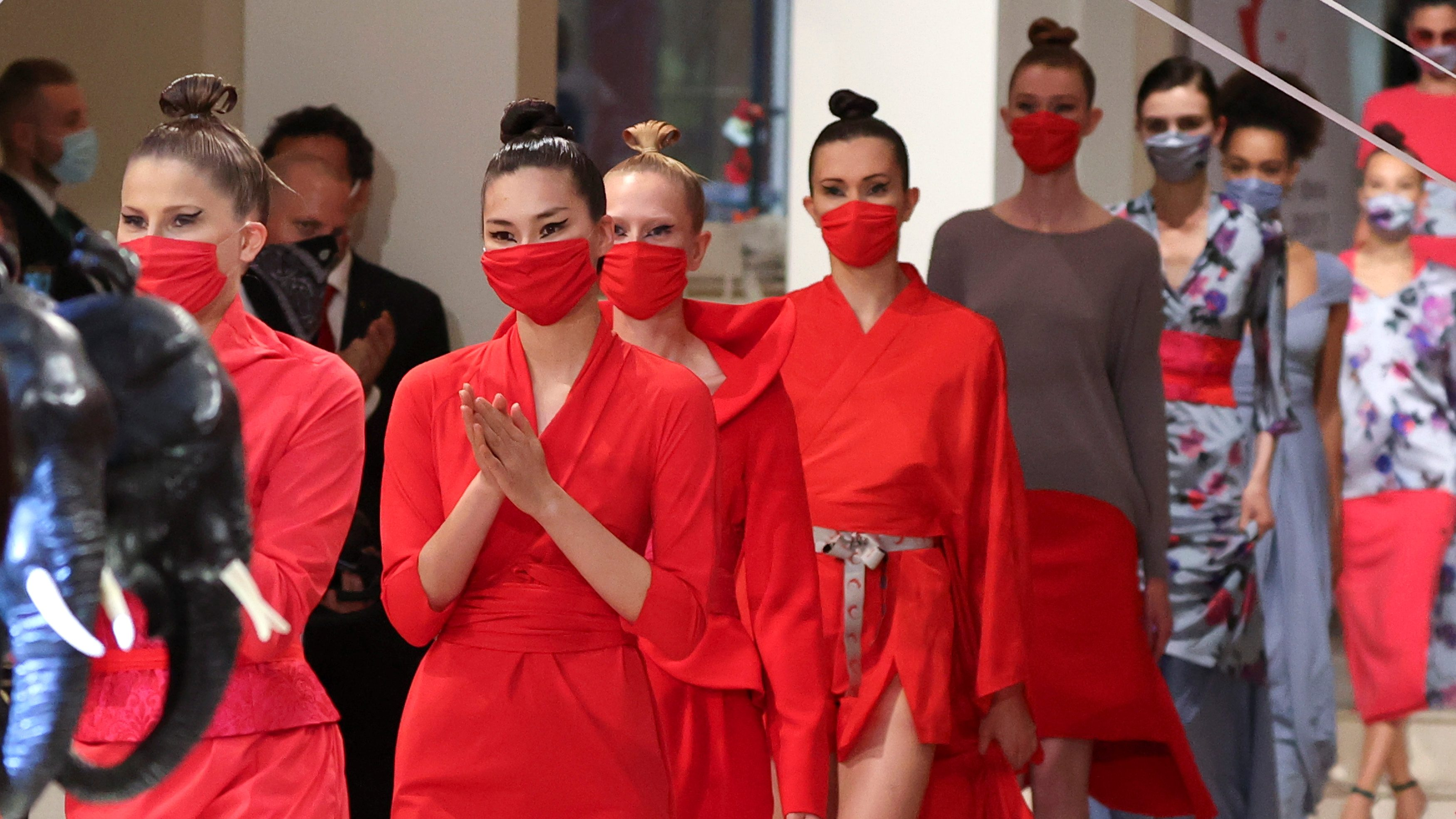 Models wear face masks as they present creations of the 2021 summer collection by designer Anja Gockel