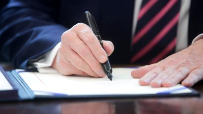 U.S. President Donald Trump signs the Paycheck Protection Program and Health Care Enhancement Act financial response to the coronavirus disease (COVID-19) outbreak, in the Oval Office at the White House in Washington, U.S. April 24, 2020.