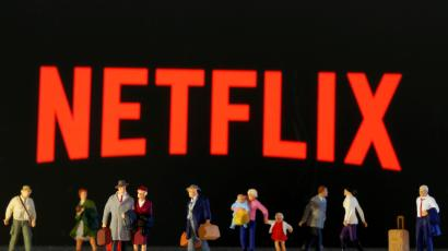 Toy figures of tiny people stand in front of the Netflix logo.