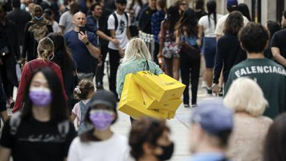 People walk with bags after shopping at the Selfridges department store in London