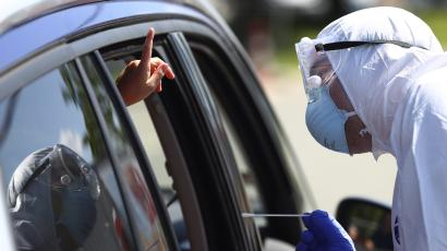 A person gets a Covid-19 test from their car. A health care worker in PPE is talking to them while their gesture.