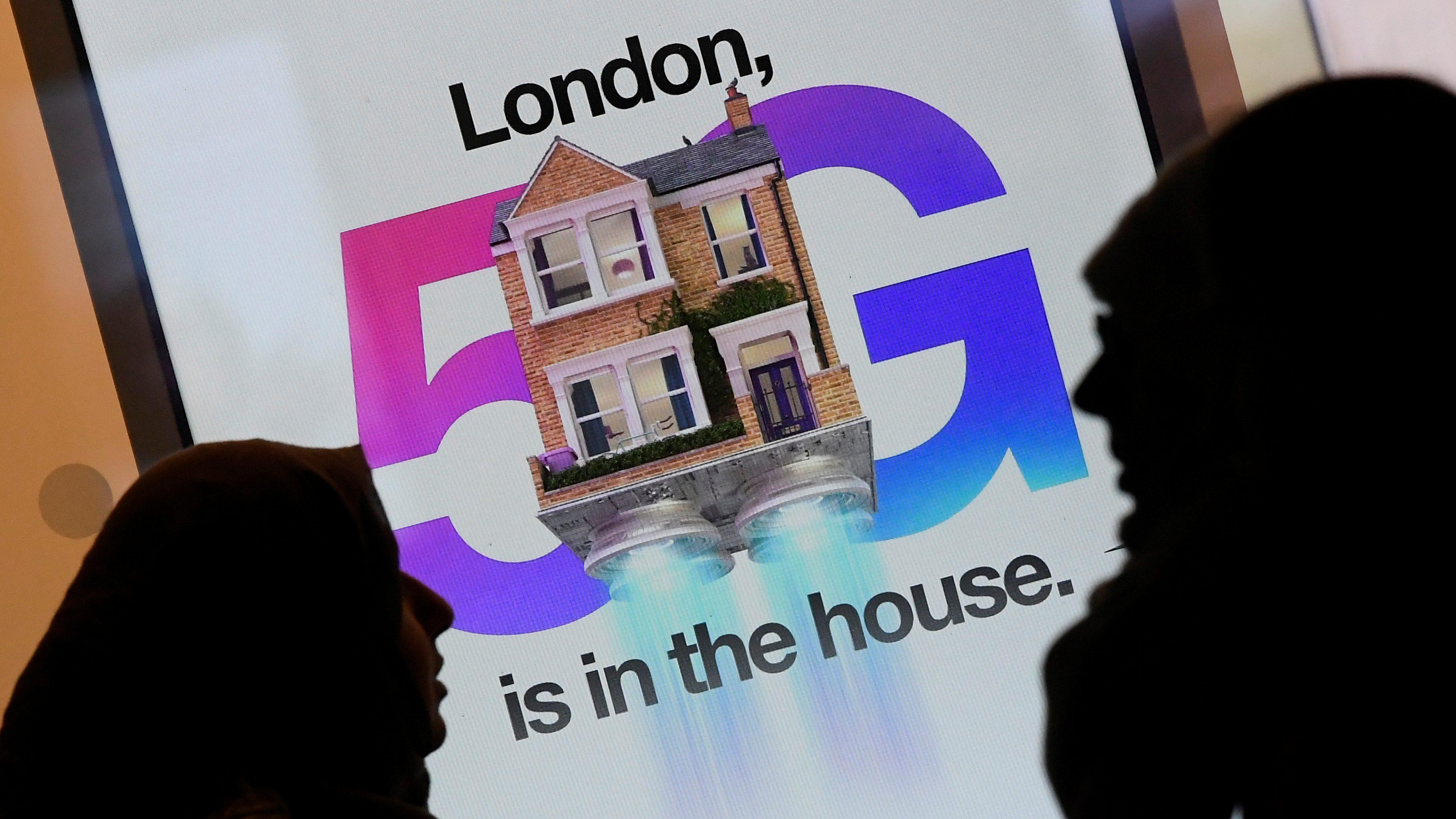Pedestrians walk past an advertisement promoting the 5G data network.