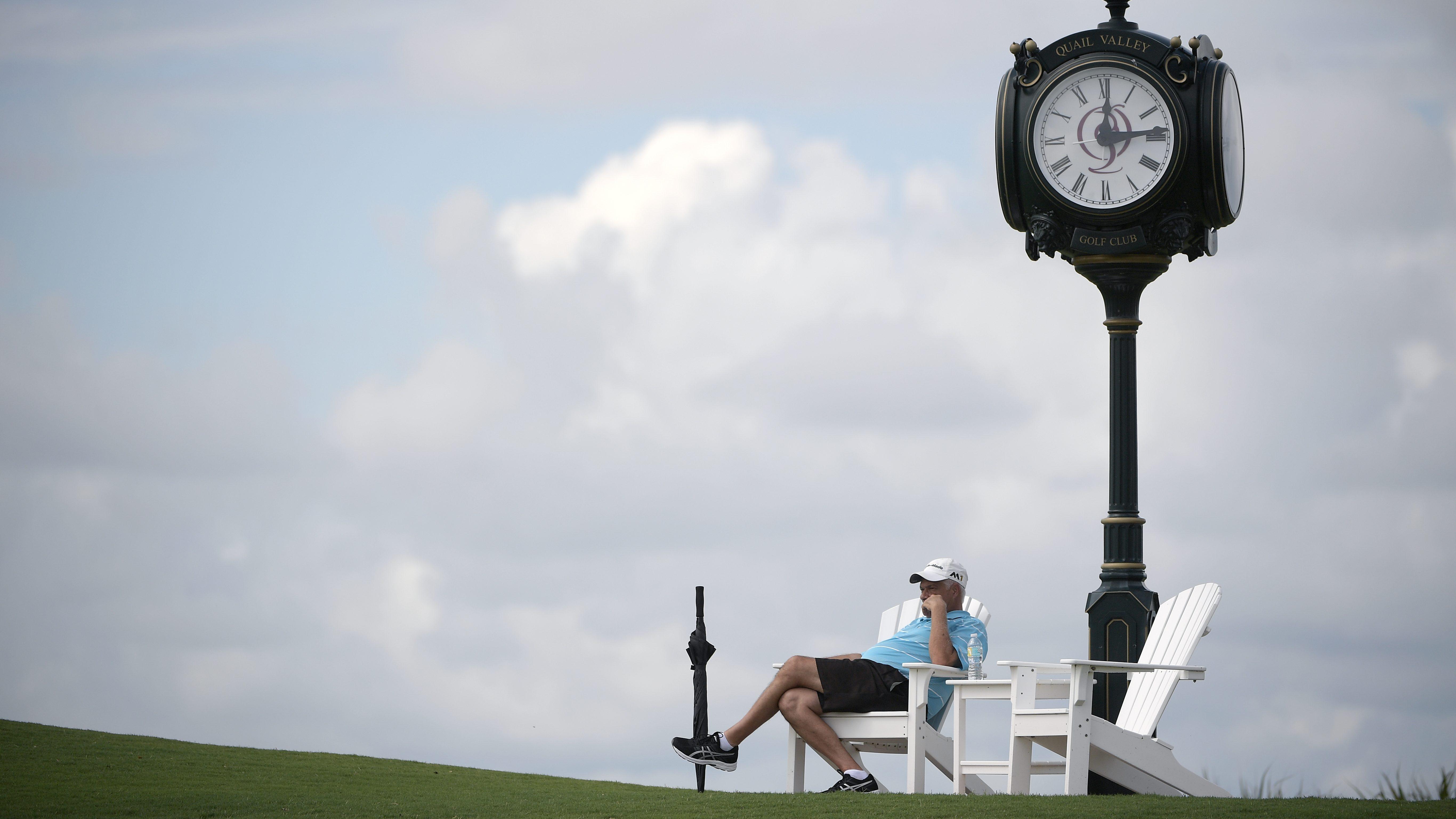 A spectator watches golf under a cloc