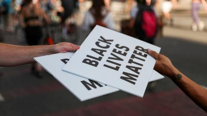 Protesters carry Black Lives Matter signs on a road during racial inequality protests in downtown Washington DC on June 23.