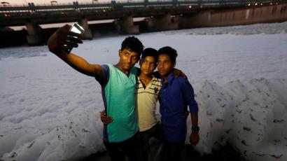 Boys pose for a selfie in front of the foam covering the polluted Yamuna river in New Delhi