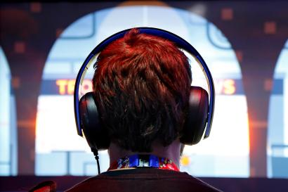 A gamer wears headphones while playing a game at the 2014 Electronic Entertainment Expo.