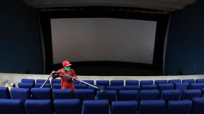 A worker cleans the seats during a routine cleaning of Navina cinema hall that was closed following the outbreak of the coronavirus disease (COVID-19), in Kolkata, India, July 16, 2020.