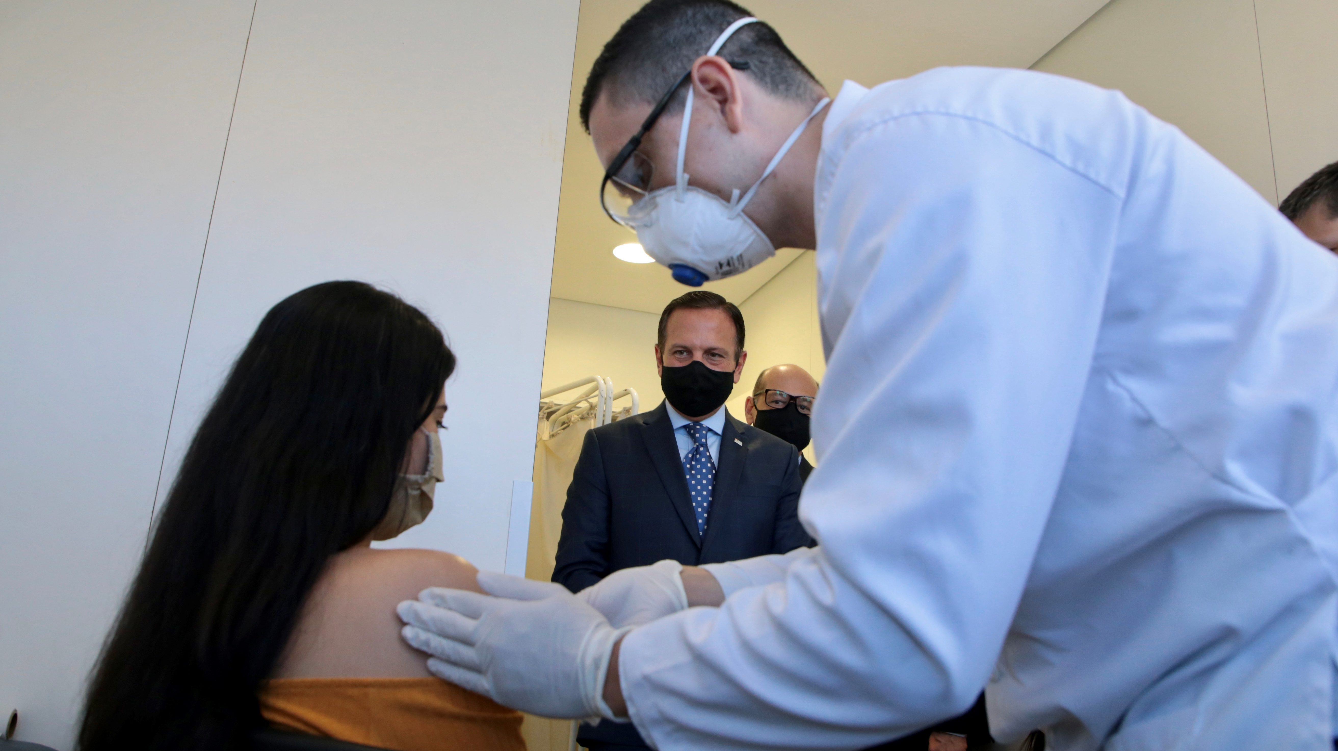 A volunteer receives the first test of the China's Sinovac coronavirus potential vaccine from a healthcare worker as Sao Paulo's Governor Joao Doria looks on amid the coronavirus disease (COVID-19) outbreak, at Hospital das Clinicas, in Sao Paulo, Brazil July 21, 2020.