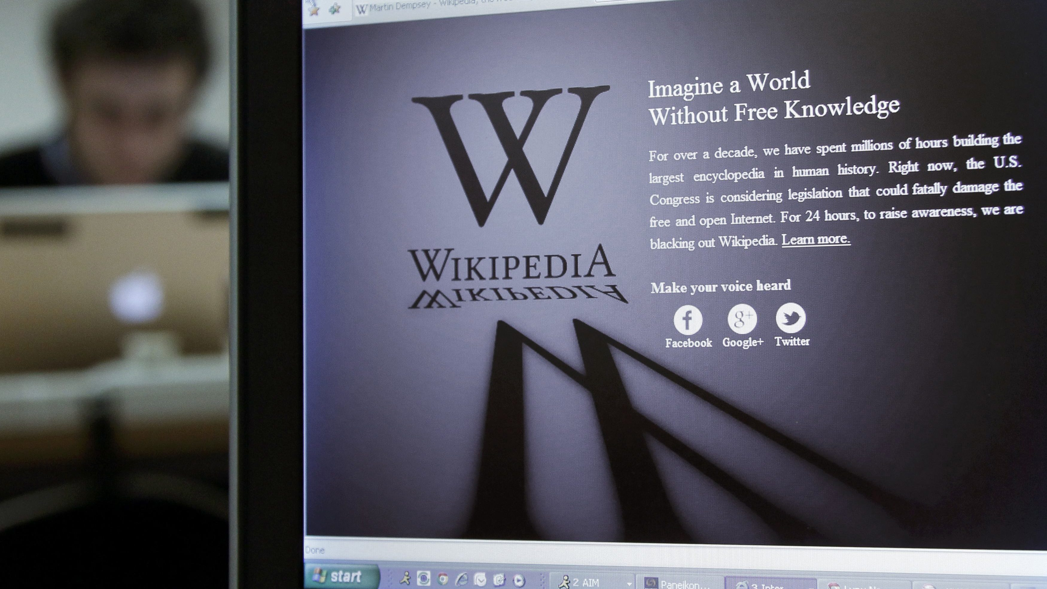 A laptop screen displays the Wikipedia homepage.