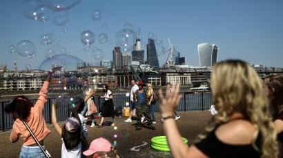 People try to pop bubbles from a street performer on the Southbank in view of London financial district.