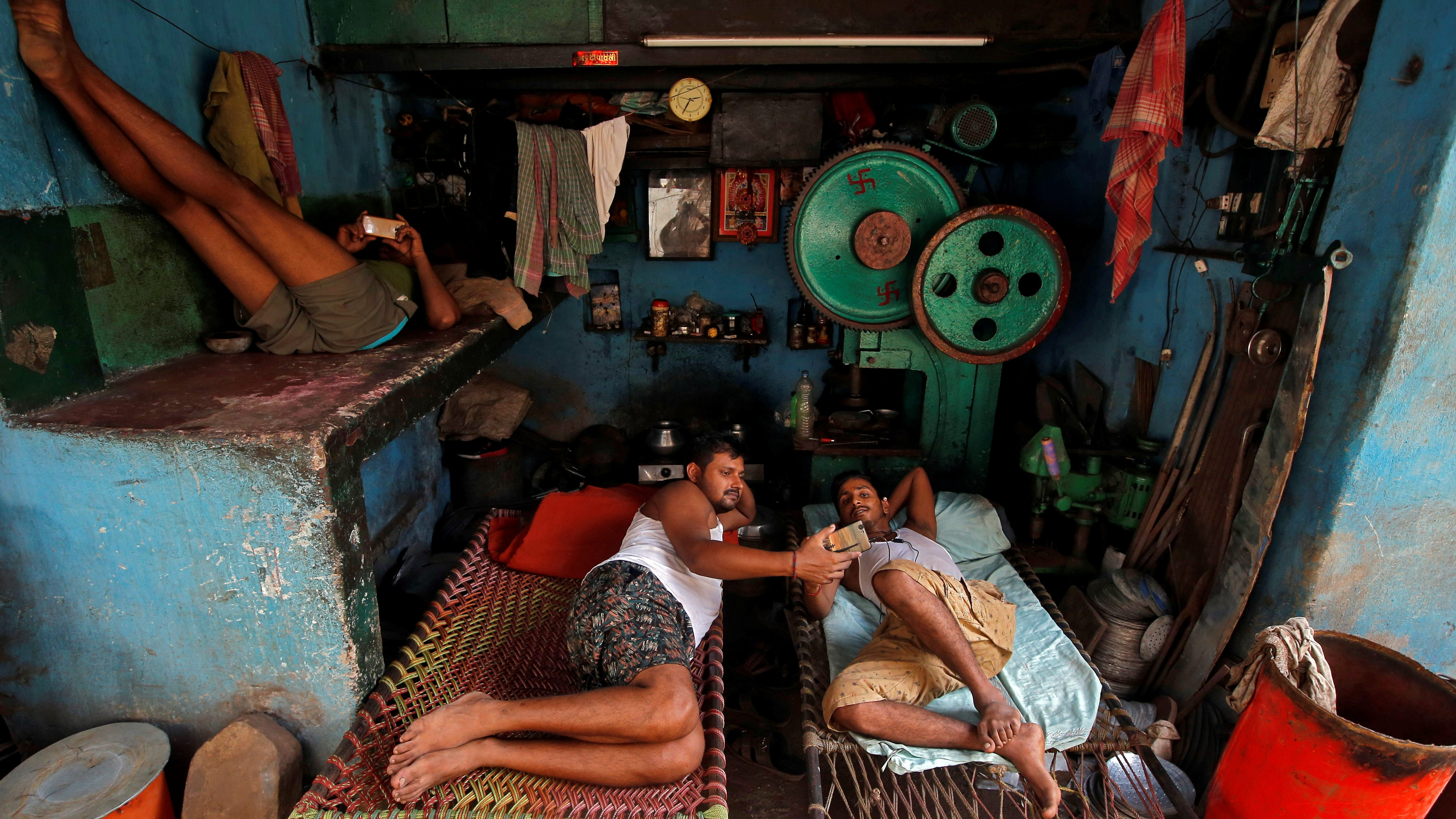 Workers watch their mobile phones as they rest in cots during a break inside a workshop in Kolkata