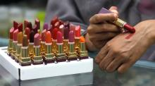 A shop attendant applies lipstick on her hand for a customer to check the shade at a store in Peshawar