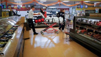 FILE PHOTO: Cataldo Ambulance medics Ricky Cormio and Luke Magnant take a 40-year-old woman out of a grocery store where she was found unresponsive in the store's bathroom after overdosing on opioids in the Boston suburb of Malden, Massachusetts, U.S. November 15, 2017. REUTERS/Brian Snyder/File Photo