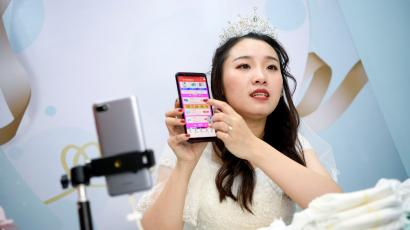 A live-streaming anchor wearing a wedding gown promotes Pampers baby diapers through a live streaming session