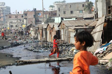 A girl walks across polluted water in a slum in Dhaka, Bangladesh