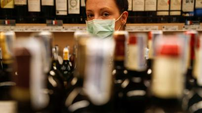 A woman looks at the camera through wine bottles lined up at a grocery store.