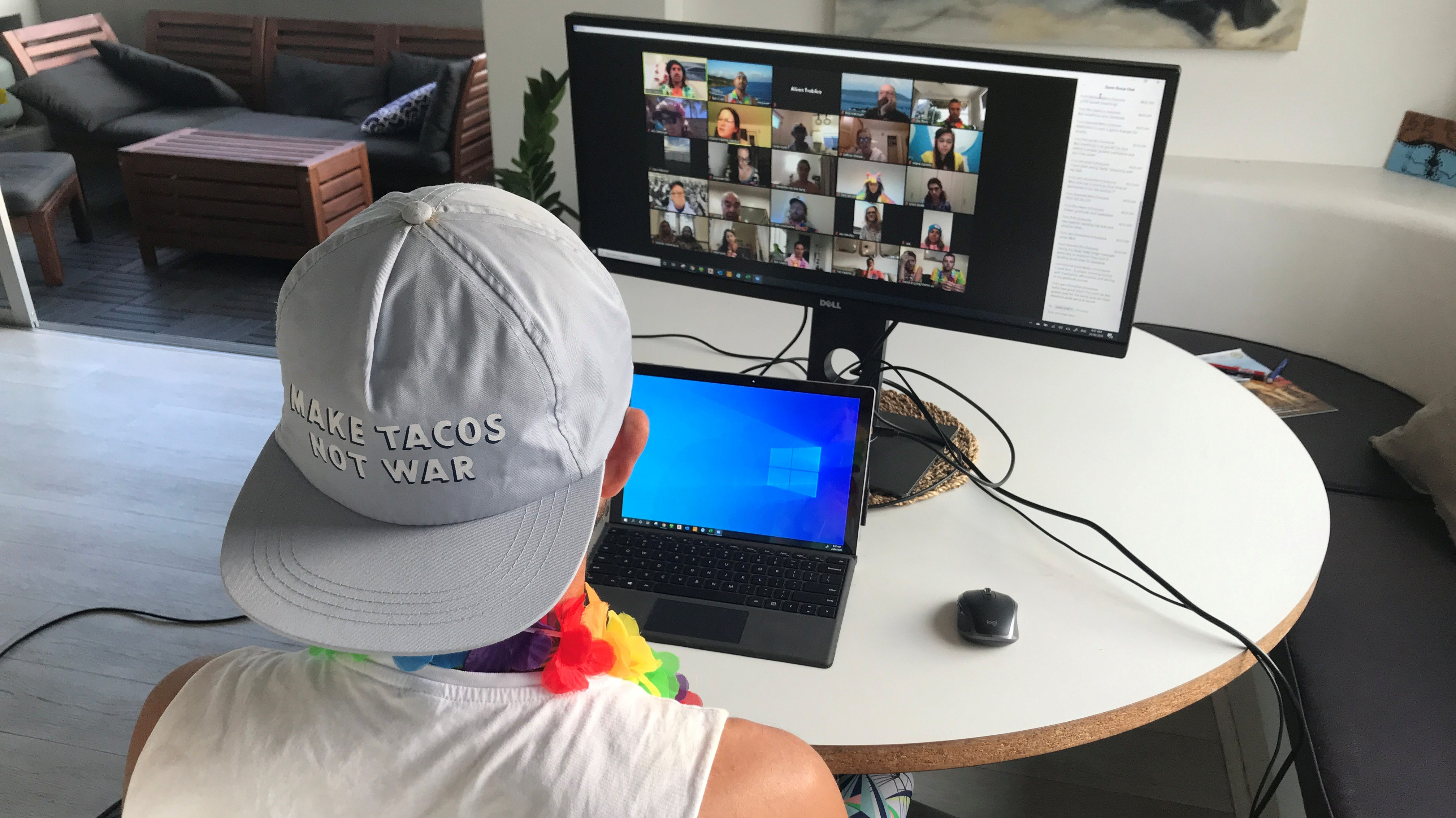 A man participates in a video call while wearing a backwards cap and a brightly colored lei.