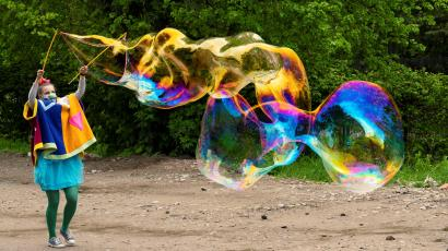 A clown wearing a protective face mask makes soap bubbles in a park.