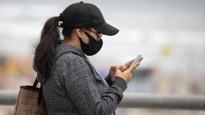 A woman wears a face masks as she views her mobile phone during the global outbreak of the coronavirus disease