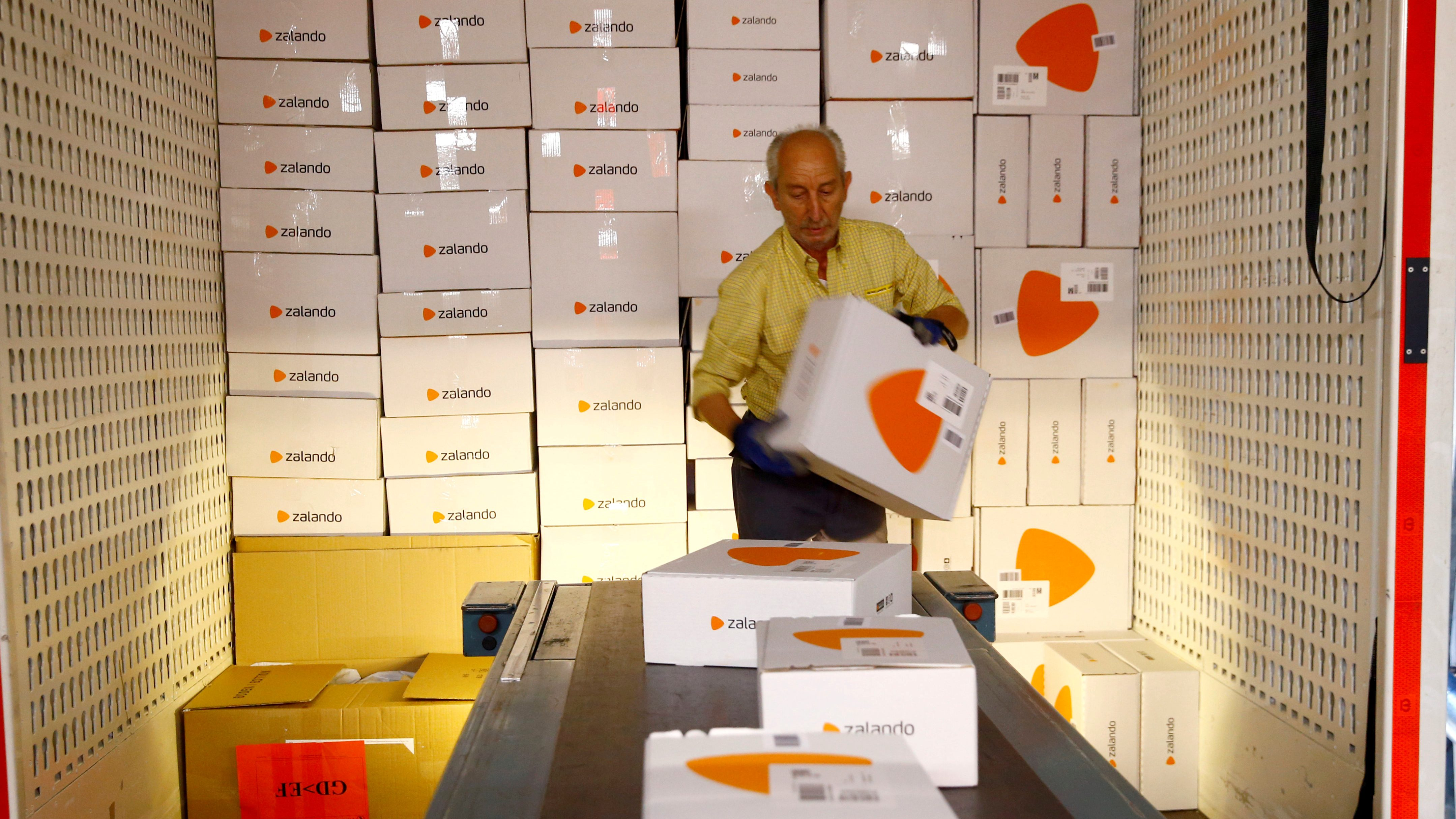 An employee places parcels of online mail order company Zalando on a conveyor