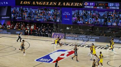 Two teams play in a nearly empty arena in front of a large video screen displaying the heads of virtual fans.
