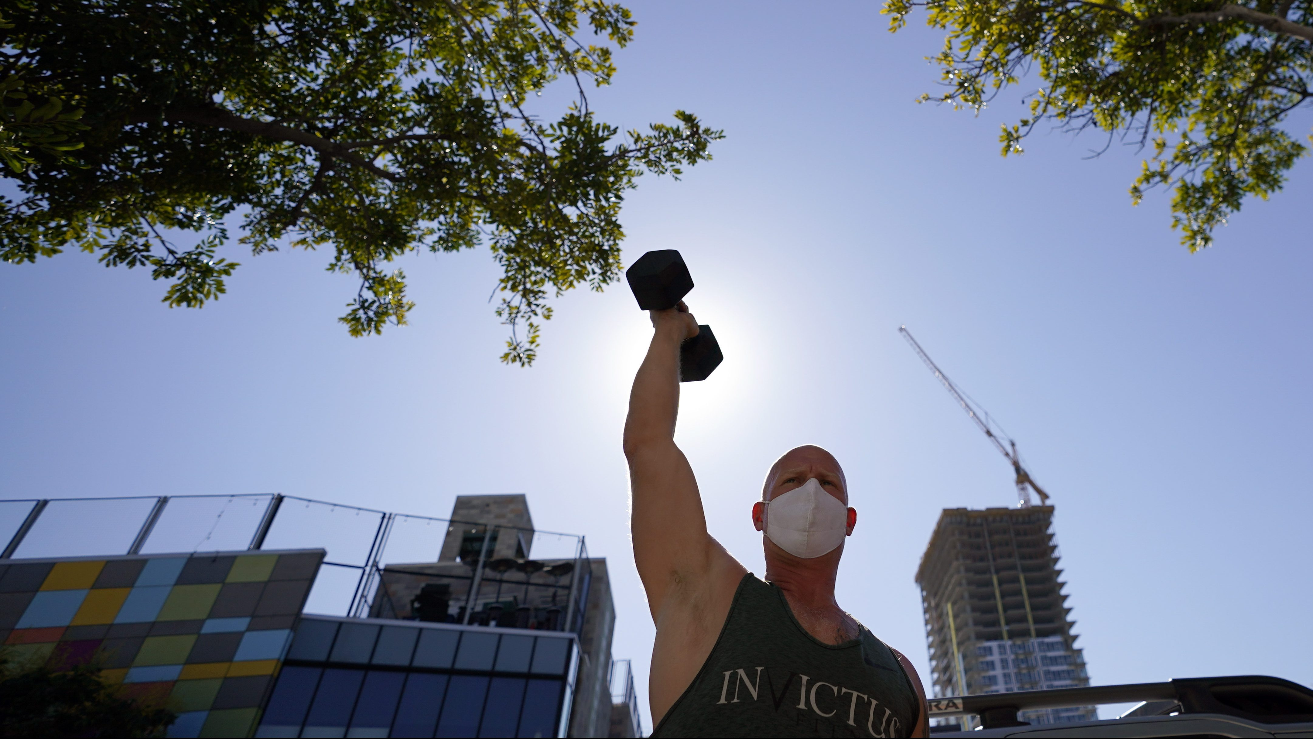 A man lifts weights outdoors