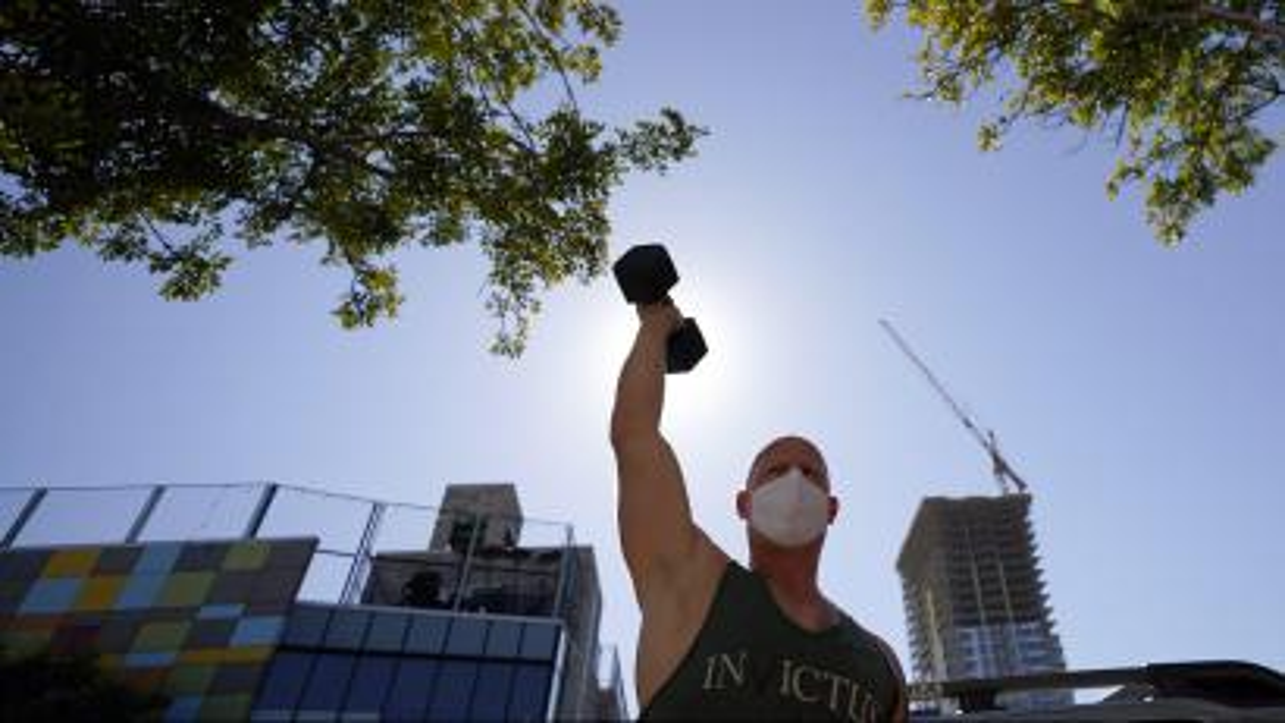 A man lifts weights outdoors